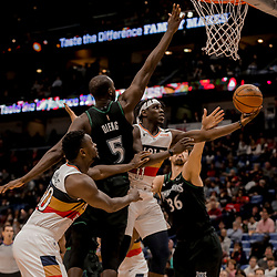 Dec 31, 2018; New Orleans, LA, USA; New Orleans Pelicans guard Jrue Holiday (11) shoots over Minnesota Timberwolves center Gorgui Dieng (5) and forward Dario Saric (36) during the second half at the Smoothie King Center. Mandatory Credit: Derick E. Hingle-USA TODAY Sports