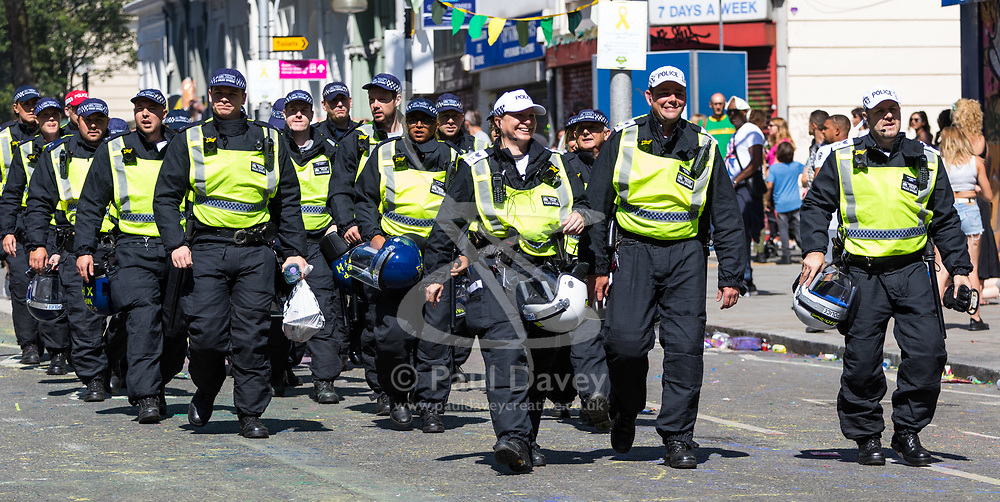 London, August 27 2017. Police make their way to their stations as Family Day of the Notting Hill Carnival gets underway. The Notting Hill Carnival is Europe's biggest street party held over two days of the bank holiday weekend, attracting over a million people. © Paul Davey.