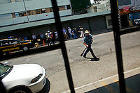 A man carries a rifle across a street in front of a gun shop in Guatemala City May 19, 2009. In recent days the country of Guatemala is dealing with unrest as the Presidnet Alvaro Colom and Guatemala's business elite are embroiled in a scandal involving money laundering, embezzling government funds and ordering assassinations, following the murder of a prominent lawyer Rodrigo Rosenberg. (Darren Hauck)