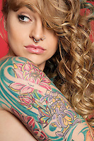 Beautiful young woman looking sideways with tattooed arm