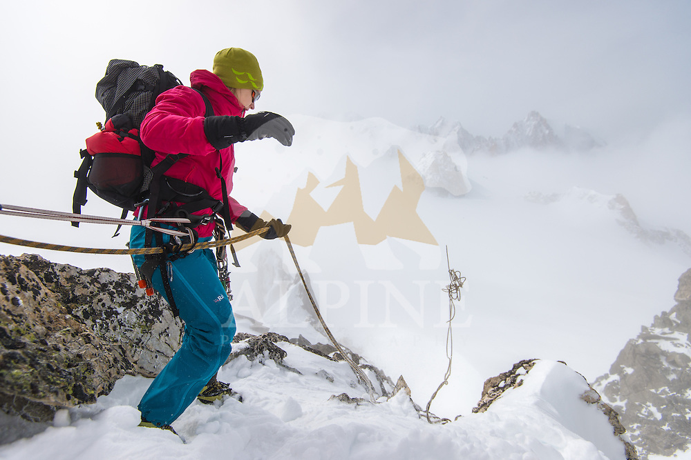 A female mountaineer throws a climbing rope from the ridge of Aigille Marbrees on a cloudy winter day.