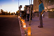11 OCTOBER 2010 - PHOENIX, AZ:  A woman looks at luminarias placed in front of Phoenix police headquarters during a protest Monday night. About 300 people gathered at the Phoenix Police Department headquarters building Monday night to protest the shooting of Daniel Rodriguez and his dog. The officers responded to a 911 call made by Rodriguez' mother. A scuffle ensued when they arrived and Phoenix police officer Richard Chrisman shot Rodriguez, who was unarmed, and his dog. Chrisman then allegedly filed a false report about the event. He has been arrested on felony assault charges. The event has angered some in the Latino community and they have held a series of protests at the police headquarters. They want Chrisman charged with murder.    Photo by Jack Kurtz