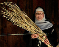 BETHLEHEM, CT- 11 OCTOBER 2005- Mother Noella Marcellino of the Abbey of Regina Laudis  holds a strand of Rye which will be used to make mats which cover the abbey's cheese.  Mother Noella has won international acclaim for her cheese making. She received a doctorate in microbiology from the University of Connecticut and also was awarded a Fulbright scholarship to go to France to study native fungus strains. (Photo by Robert Falcetti)