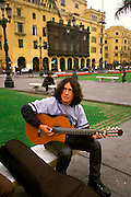 PERU, LIMA, LIFESTYLE student musician playing the guitar and performing in the Plaza de Armas