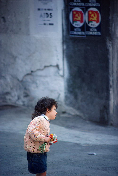 A young girl with flowers looks across a courtyard in Italy village with posters depicting communism and AIDS in the background