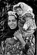 Rural mother carrying her infant on her shoulder in typical Egyptian manner. Each wears brightly patterned outfit.