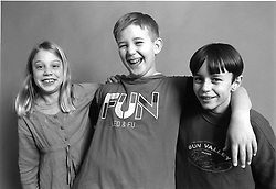Group of young children standing together with their arms around each other smiling,