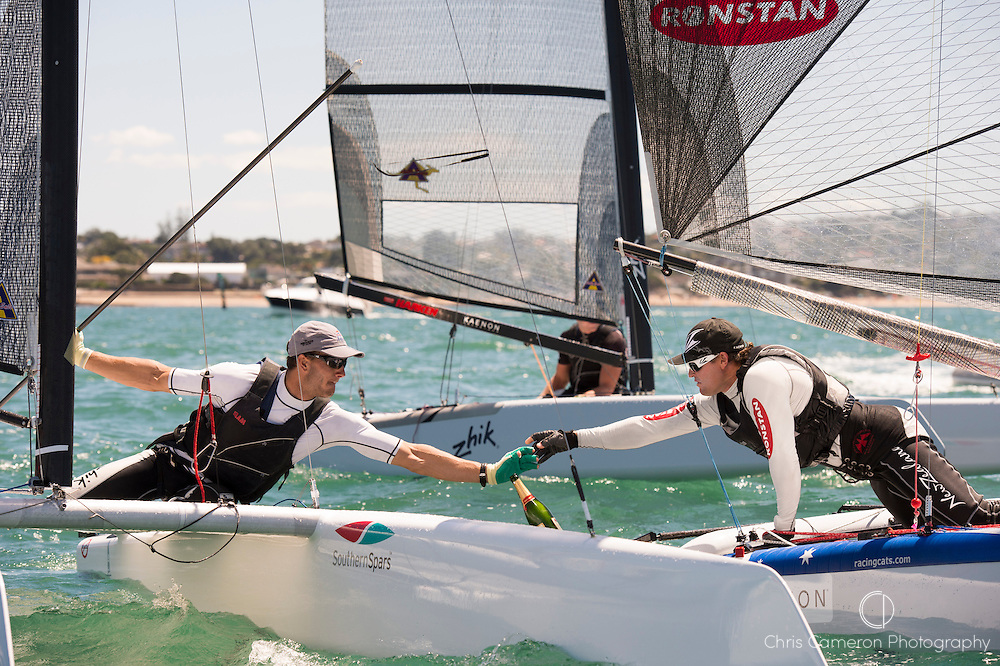 A Class World championships winner Glenn Ashby (AUS111) trys to share Champagne  with second placed Blair Tuike (NZL777) The regatta of nine races was sailed at Takapuna in Auckland. 16/2/2014