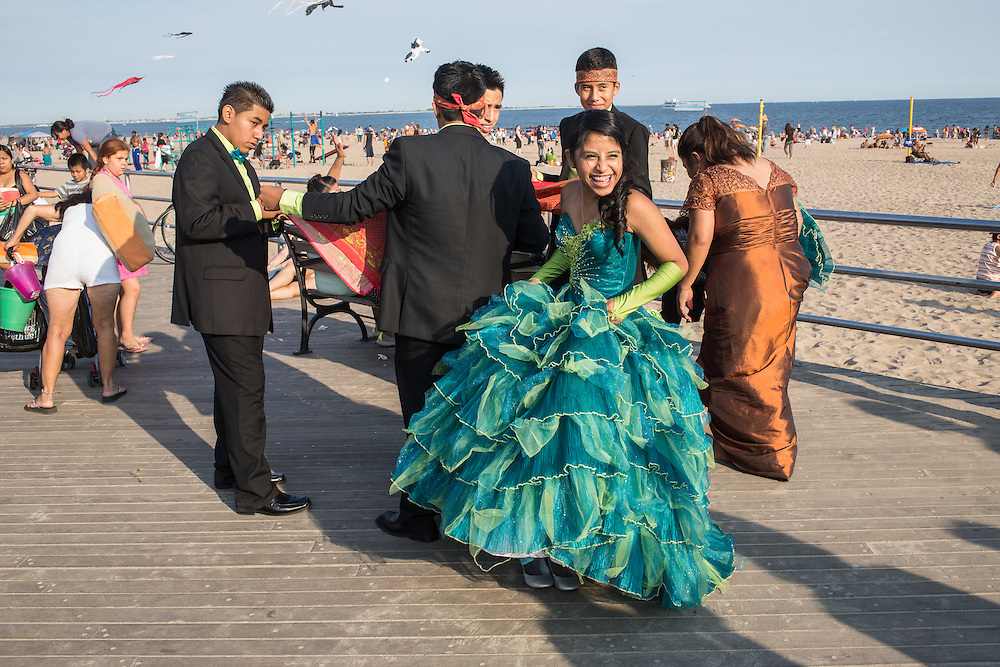 A girl getting prepared for photographs at her quinceañera celebration on the boardwalk at Coney Island.