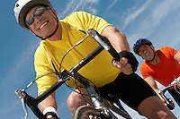 Two men on bicycle ride portrait low angle view
