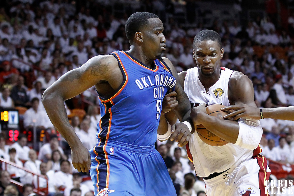 19 June 2012: Miami Heat power forward Chris Bosh (1) drives past Oklahoma City Thunder center Kendrick Perkins (5) during the third quarter of Game 4 of the 2012 NBA Finals, Thunder at Heat, at the AmericanAirlinesArena, Miami, Florida, USA.