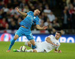 Andraz Kirm of Slovenia looks in pain as he gets tackled by Gary Cahill of England (Chelsea) - Photo mandatory by-line: Alex James/JMP - Mobile: 07966 386802 - 15/11/2014 - SPORT - Football - London - Wembley - England v Slovenia - EURO 2016 Qualifier