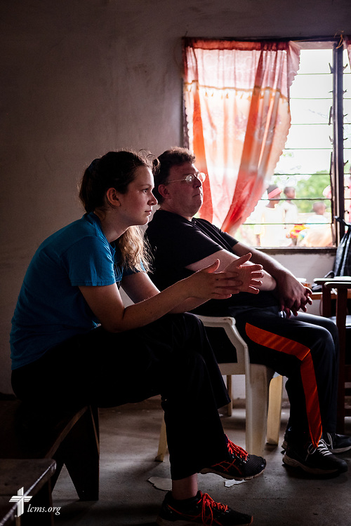 Hayden Rensner, a student at Concordia University, Nebraska, and the Rev. Michael Awe, team leader and pastor at Hope Lutheran Church, South Sioux City, Neb., pause for a moment before the door opened on the third day of the LCMS Mercy Medical Team on Wednesday, May 9, 2018, in the Yardu village outside Koidu, Sierra Leone, West Africa. LCMS Communications/Erik M. Lunsford