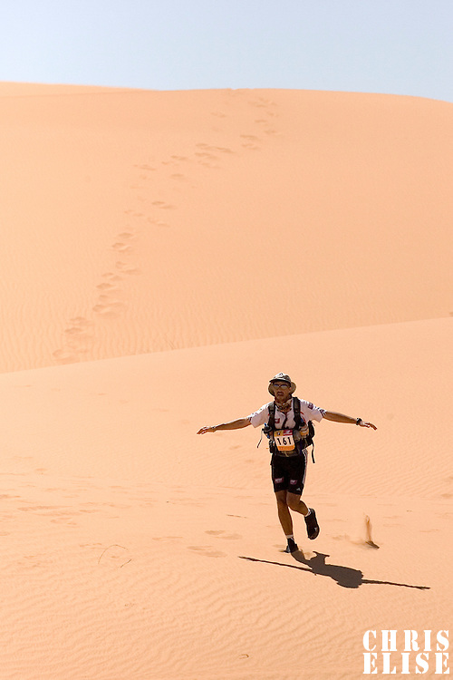 30 March 2007: #161 Herve Demirdjian of France runs in erg Znaigui en route to check point 3 during fifth stage of the 22nd Marathon des Sables between west of Kfiroun and erg Chebbi (26.22 miles). The Marathon des Sables is a 6 days and 151 miles endurance race with food self sufficiency across the Sahara Desert in Morocco. Each participant must carry his, or her, own backpack containing food, sleeping gear and other material.