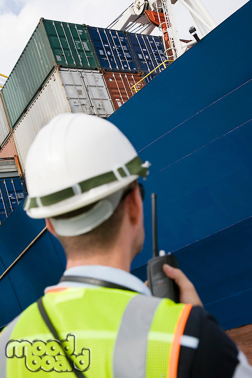 Man wearing hard hat using walkie-talkie at container terminal back view