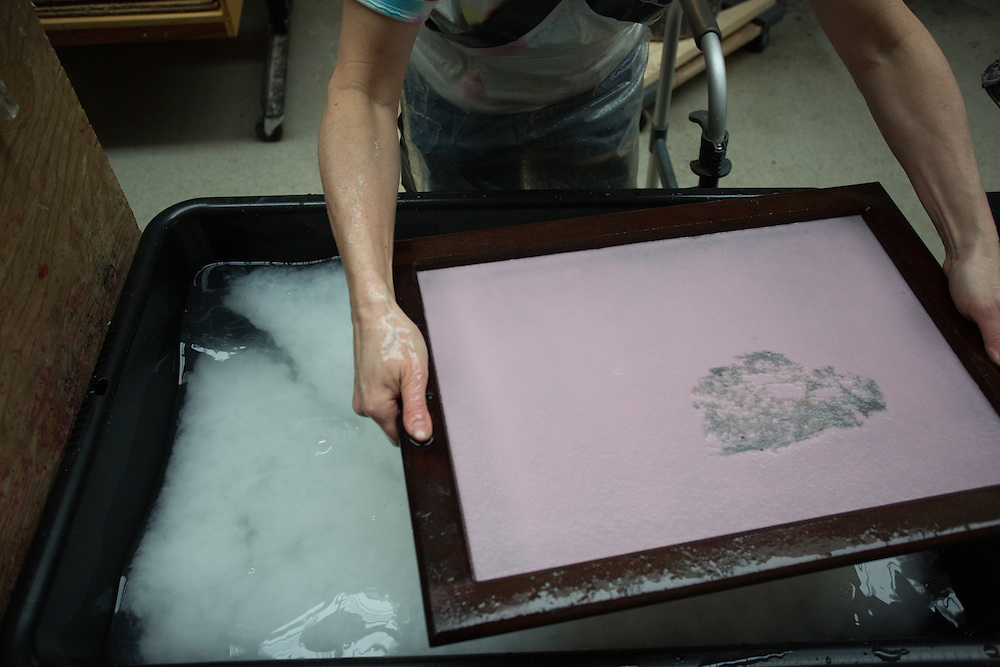 After a few minutes, the wet sheet is ready to be placed in a second vat of white cotton fiber.
