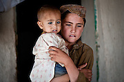 An Afghan boy holds a child while Marines interrogate his family.