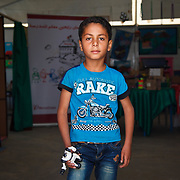 Muhanad, 7, and his family left Daraa, Syria two years ago for the safety of Jordan. He's holding a birthday gift from his grandfather, Muhamed. The toy reminds him of his grandfather, &quot;who is now in heaven.&quot;<br /> <br /> Muhanad is at his school, in one of the Mercy Corps extra curicular activity rooms where he participates in activities like drawing, painting, and games. Zaatari camp for Syrian refugees, Jordan, May 2015.<br /> <br /> Muhanad and his family have made their way to Germany since this photo was taken.