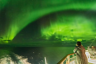 A participant in the Road Scholar aurora tour in October 2017 watches the Northern Lights from the aft deck of the m/s Nordlys on the Norway coast. The Big Dipper is at centre