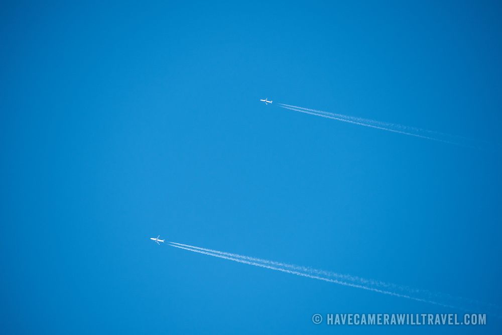 Two planes fly side-by-side against a perfectly clear blue sky, each with sharp contrails behind it.