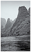 boat dwarfed by landscape, River Li, Guangxi Provence, China.