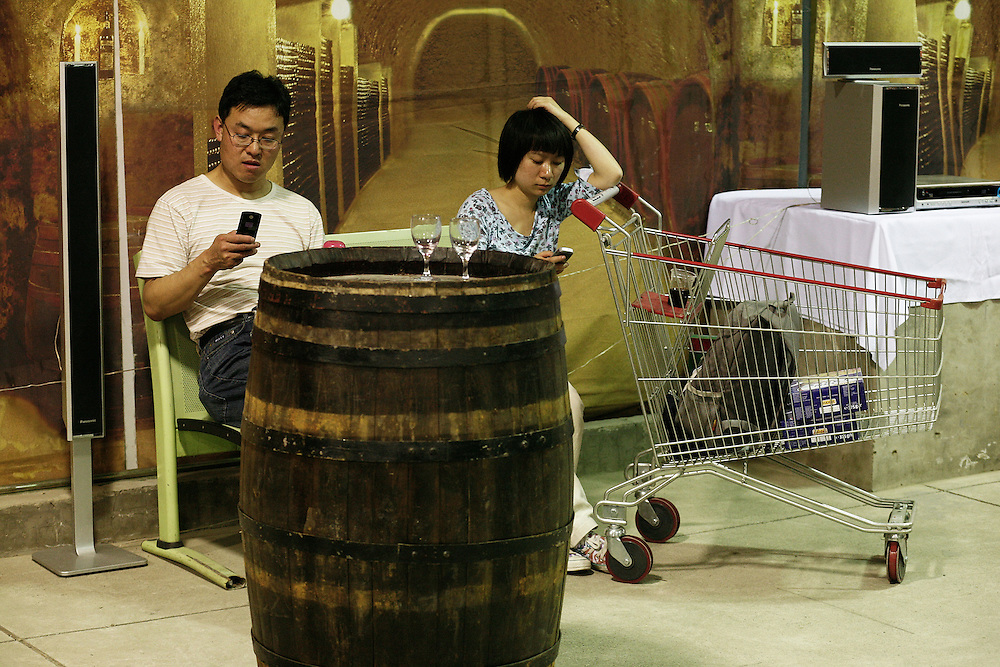 A couple is sending textos while resting in a wine tasting party in a supermarket of Beijing.