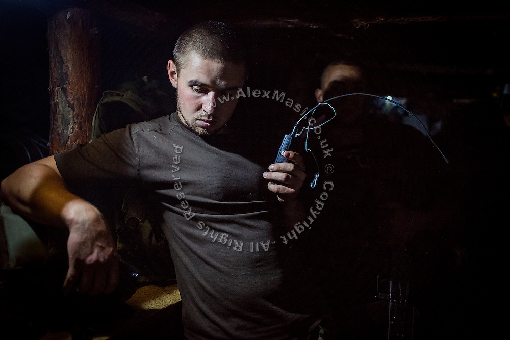 A soldier living in an underground bunker near the trenches is listening to radio communications on the frontline of Hranitne, near Mariupol, southeast Ukraine.