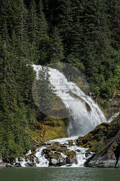 A glacial waterfall rushes down a mountain side into LeConte Bay near the LeConte Glacier in Petersburg Island, Alaska. The icebergs calve off the nearby LeConte Glacier which is the southernmost tidewater glacier of the Northern Hemisphere.