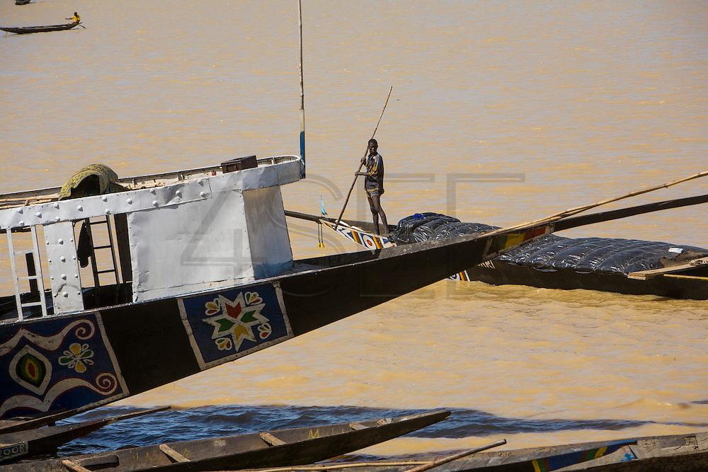 "A man drives a ""pinasse"" in the harbour of Mopti. At the confluence of the Niger and the Bani rivers, between Timbuktu and Ségou, Mopti is the second largest city in Mali, and the hub for commerce and tourism in this west-african landlocked country."