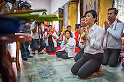 17 FEBRUARY 2013 - BANGKOK, THAILAND:  Thai Prime Minister YINGLUCK SHINAWATRA offers prayers for Pongsapat Pongchareon in Wat Chana Songkram in Bangkok Sunday. Pol General Pongsapat Pongcharoen, a former deputy national police chief who also served as secretary-general of the Narcotics Control Board is the Pheu Thai Party candidate in the upcoming Bangkok governor's election. Yingluck is the head of the Pheu Thai party and campaigns with Pongsapat. (He resigned from the police force to run for Governor.) Former Prime Minister Thaksin Shinawatra reportedly recruited Pongsapat. Most of Thailand's reputable polls have reported that Pongsapat is leading in the race and likely to defeat Sukhumbhand Paribatra, the Thai Democrats' candidate and incumbent. The loss of Bangkok would be a serious blow to the Democrats, whose base is the Bangkok area.     PHOTO BY JACK KURTZ