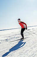 Male athlete cross-country skiing on a sunny day.