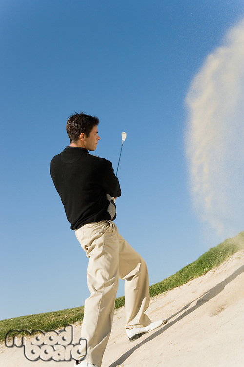 Young Man Hitting Ball out of Sand Trap