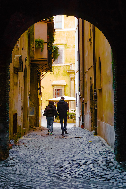 A young couple walk along a street in Rome, Italy