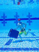 Man underwater,  wearing cap and sunglasses carrying a suitcase while walking on swimming pool bottom.