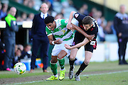 Yeovil Town's Shaun Jeffers and Carlisle Utd's Macaulay Gillesphey battle to get to the ball watched by Yeovil Town manager Darren Way during the Sky Bet League 2 match between Yeovil Town and Carlisle United at Huish Park, Yeovil, England on 25 March 2016. Photo by Graham Hunt.