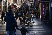 In Amsterdam rijdt een man op een vouwfiets door het centrum over het zebrapad. Een vader met kind gaat net oversteken.<br /> <br /> In Amsterdam a cyclist on a folding bike is riding at the city centre. A father is just crossing the road with his child.