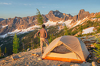 Adult male at daybreak standing next to backpacking tent and gazing at view of Cutthroat Peak on ridge above Cutthroat Pass, near Pacific Crest trail. North Cascades Washington