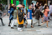 Buddhist monk meditating walking amongst shoppers in Ginza (Tokyo, Japan)