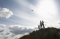 Silhouette of parents and child flying kite on dunes