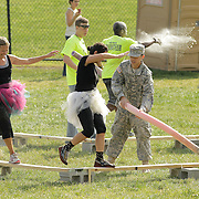 A UK ROTC member whacks racers with a foam noodle as they try to clear an obstacle during the Bluegrass Mud Run, a 5K military-style obstacle course race sponsored by WUKY and the University of Kentucky ROTC in Lexington, Ky., on Saturday, September 22, 2012. Photo by David Stephenson