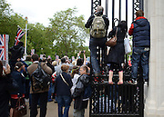 © Licensed to London News Pictures. 05/06/2012. London, UK. People stand on gates to watch the Jubilee Procession on the Mall today 5th June 2012.  The Royal Jubilee celebrations. Great Britain is celebrating the 60th  anniversary of the countries Monarch HRH Queen Elizabeth II accession to the throne this weekend Photo credit : Stephen Simpson/LNP