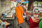 05 OCTOBER 2012 - BANGKOK, THAILAND:  A Buddhist monk walks through the amulet market in Bangkok. Hundreds of vendors sell amulet and Buddhist religious paraphernalia to people in the area north of the Grand Palace near Wat Maharat in Bangkok.        PHOTO BY JACK KURTZ