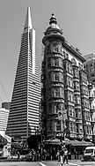 Black and white downtown North Beach San Francisco Columbus Tower Sentinel Tower + Transamerica Bldg, people crossing street in front of Cafe Zoetrope. Street scene.