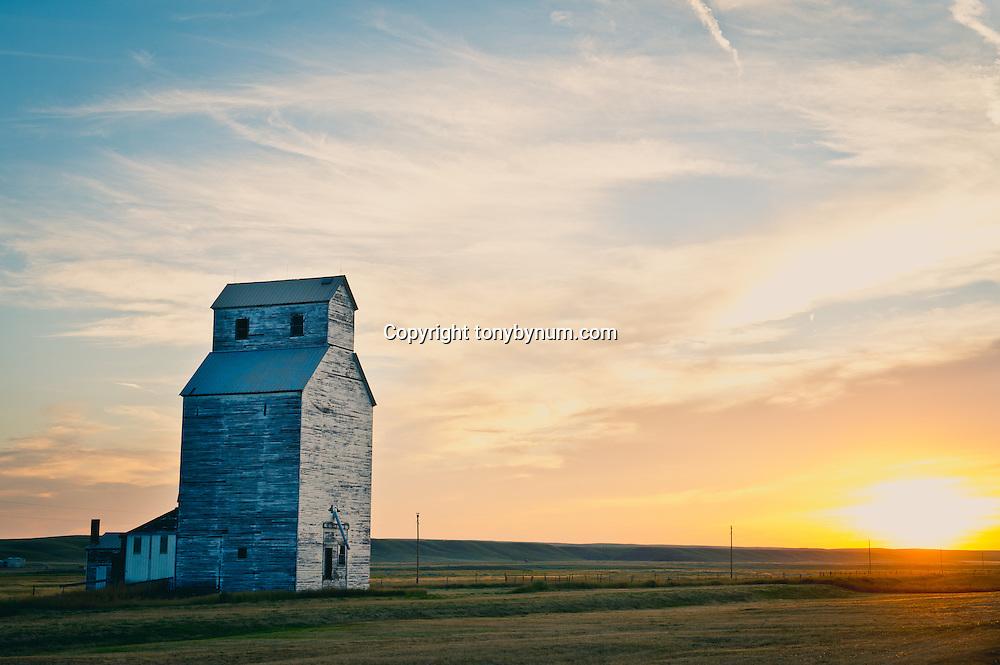 sun sets behind an old grain building on the prairie of montana