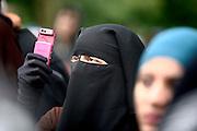 Dietzenbach | 24.07.2011..Am Samstag (24.07.2011) hielt der Salafist und radikale Islamist Pierre Vogel (Abu Hamza) in Dietzenbach (Landkreis Offenbach) vor etwa 200 Menschen einen Vortrag..Hier: Eine voll verscheierte Frau (Niqab) im Publikum fotografiert mit ihrem Mobiltelefon...©peter-juelich.com..[No Model Release | No Property Release]