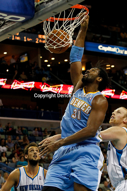 January 6, 2012; New Orleans, LA, USA; Denver Nuggets center Nene (31) dunks over New Orleans Hornets center Chris Kaman (35) during the second half of a game at the New Orleans Arena. The Nuggets defeated the Hornets 96-88.  Mandatory Credit: Derick E. Hingle-US PRESSWIRE