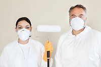 Portrait of female worker holding paint roller with male worker standing with her