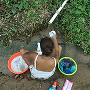 OCTOBER 13 - UTUADO, PUERTO RICO - <br /> Suheidy de la Rosa, 32, washes clothes on the side of the road  using water from a mountain stream across from her house in the Barrio Salto Arriba after the path of  Hurricane Maria. <br /> (Photo by Angel Valentin/Freelance)