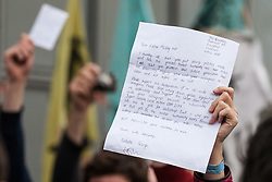 London, UK. 23rd April 2019. Climate change activists from Extinction Rebellion in Parliament Square hold up letters to their Members of Parliament, including one addressed to Esther McVey MP, requesting meetings to discuss the issue of climate change. Activists tried to deliver their letters to Parliament, but all but ten were prevented from doing so by the Metropolitan Police.