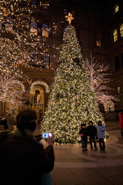 A man takes photos of his children in front of the Christmas tree in the courtyard of the New York Palace Hotel.